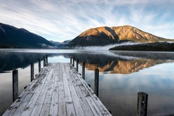 A calm dawn at the jetty at Lake Rotoiti, Nelson Lakes National Park, New Zealand. Mist, mountains and sky reflected in the lake.