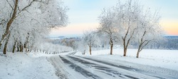 A calm snowy winter morning landscape with a colorful background, snow covered trees and a road heading down a hill