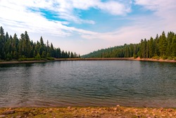 A calm, summer day landscape with pine trees lining the shores of Sawmill Lake in the Tahoe National Forest near Truckee, California on the north shore of Lake Tahoe