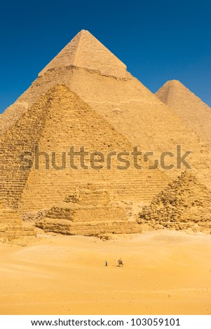 A camel riding tourist passes the base of Great Pyramids in Giza showing the relative scale of the structures in Cairo, Egypt