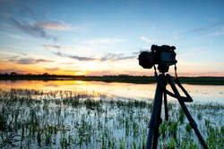A camera on a tripod during a sunset photo against the background of a slightly cloudy sky over the river in spring