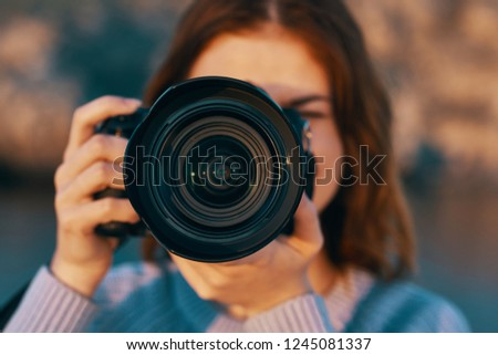 A camera with a big lens and a happy photographer in nature