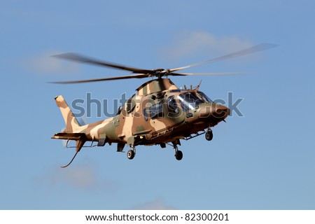A camouflaged military helicopter in flight