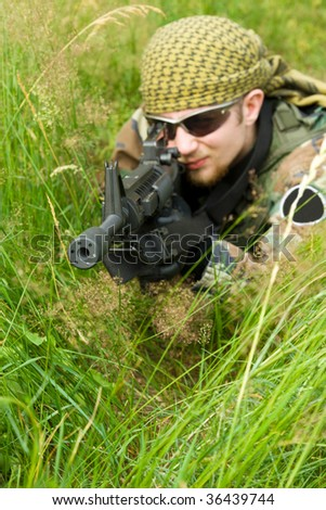 A camouflaged military sniper laying in a long grass with a machine gun and aiming. ASG battle. Focus on the muzzle / silencer.