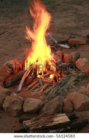 a camp fire in a fire pit at a campsite