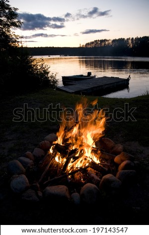 A campfire near a lake, surrounded by trees, with a dock and a boat.