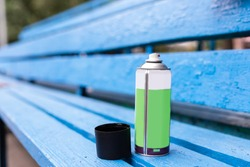 A can of spray paint is on a blue bench.