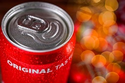 A can,  tin of fresh Coca Cola drink with brick wall backround. Coca-Cola company is the most popular brand in the world.