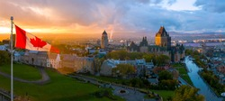 A Canadian flag flies over Old Quebec City at sunset. Aerial drone panorama view of Quebec City including Chateau Frontenac and Differin Terrace.