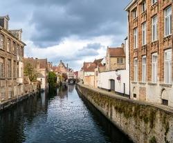 A canal in Bruges. Dark clouds, bright brick buildings.