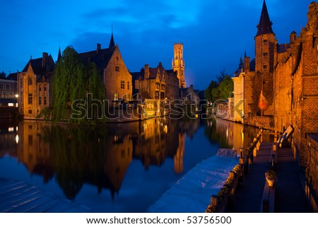 A canal reflects the buildings and belfry of the historic old city of Bruges