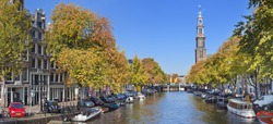 A canal with the Westerkerk tower in the city of Amsterdam, The Netherlands. Photographed on a beautiful day in early autumn.