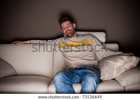 A candid photo of a man watching something funny on TV. No fake, cheesy smiles.