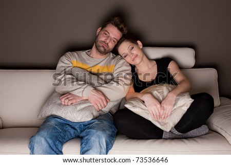 A candid photo of a young couple watching TV