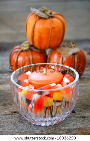 A candle holder full of candy corn and an orange candle with fake pumpkins in the background. - stock photo