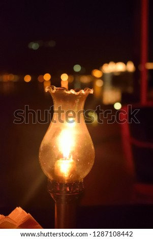 a candle in a candle stand amidst the lighting of lake pichola, udaipur in the backdrop #1287108442