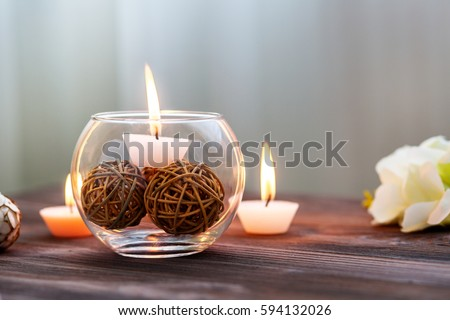 A candle in a glass vase, decoration and various interesting elements on a dark wooden background. Candles burning.