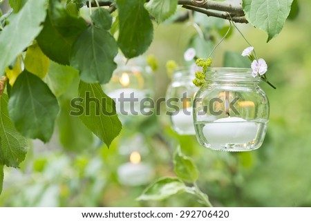 a candle in a glass with water hanging on a tree in the garden