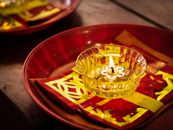 A candle in glass cup and joss papers on red trays for worshipping Chinese god in a shrine