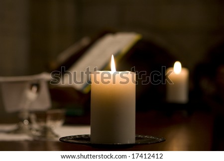 A candle on an altar is lit, illuminating a Friday morning service at St. George's cathedral in Cape Town. In the background, a Bible is open next to a second burning candle.