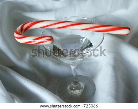 A candycane rests on a full martini glass.