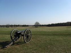 A cannon aims across a field at Manassas National Battlefield Park.