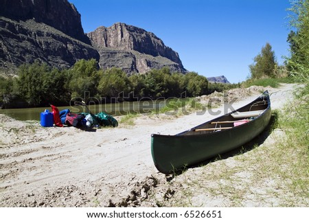 A canoe and gear resting quietly beside a river with majestic cliffs in the background.
