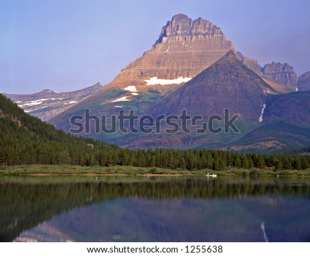 A canoe and the Rocky Mountain Peaks of Montana's Glacier National Park reflecting in Swiftcurrent Lake.