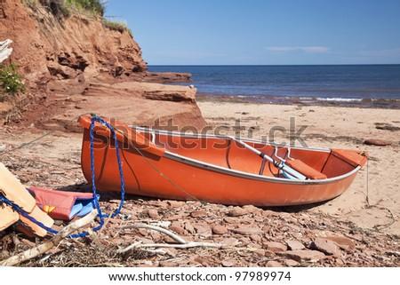 A canoe   laying on a rocky beach beside a sandstone cliff on Cabot Beach in Malpaque, Prince Edward Island, Canada.