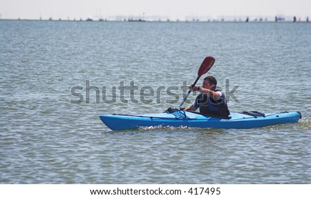 A canoeist paddles his canoe at sea