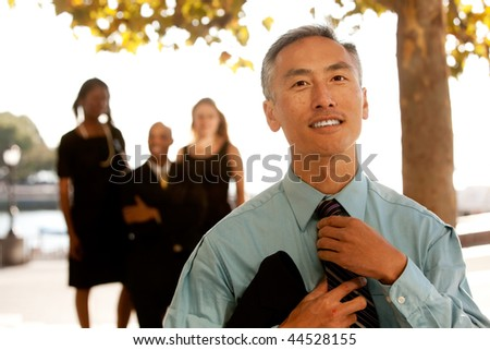 A cansual asian business man adjusting his tie