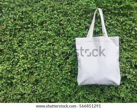 A canvas tote bag hanging on leaf wall.