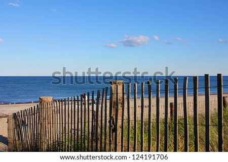 A Cape Cod New England beach lying in the afternoon sun, partly seen through a fence.