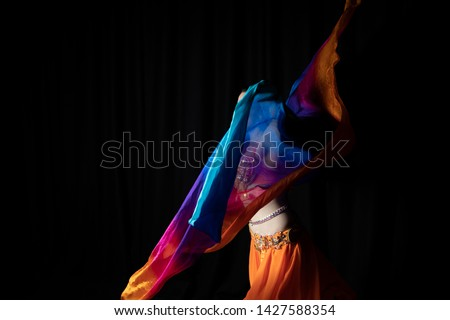 A capture of an Arabian dancer caught during a turn with a colorful, silk veil. Dressed in an orange belly dance costume, she brings the mind to the stories of 1001 night. Studio photo shoot.