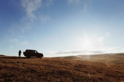 A car and a man against the backdrop of mounA car and a man against the backdrop of mountains and the sun. A lot of sky and space.tains and the sun. High quality photo