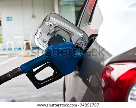 A car at gas station being filled with fuel - stock photo