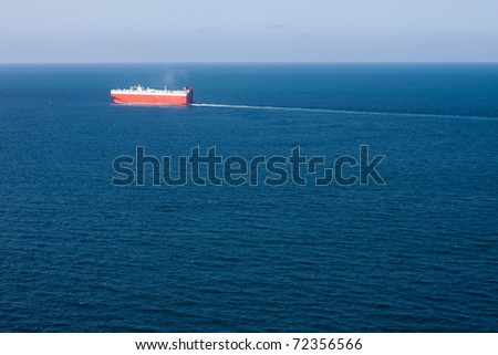 A car carrier cargo ship sails a deep blue vast ocean, leaving a think wake behind.  Horizontal image with deep vessel.