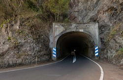 A car drives with lights through the Anaga Tunnel in the northeast of the Spanish Atlantic island of Tenerife. There is a curve at the corner exit. It's an autumn day.