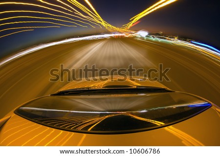 A car driving at high speed on a motorway bend, seen from the roof - stock photo