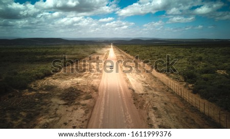 A car driving on a dirt road to the Addo Elephant National Park Stock photo ©