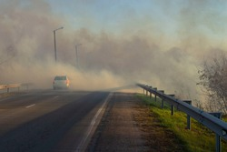 a car driving on a suburban highway during a fire on the side of the road in strong smoke