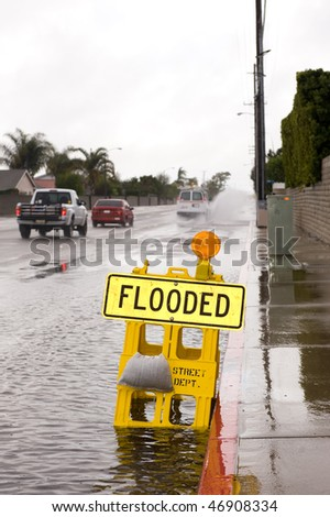 A car kicks up a pool of rainwater over a street flooded sign during bad, rainy weather.