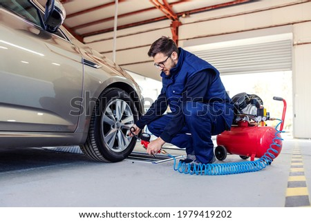 A car mechanic at the service station tries to inflate the tires on the car with the help of a compressor. A man in a blue work suit crouched next to a car in a workshop and works around car tires