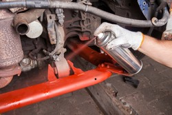 A car mechanic cleans and maintains the engine chassis of an old car against corrosion and protects it with a preparation