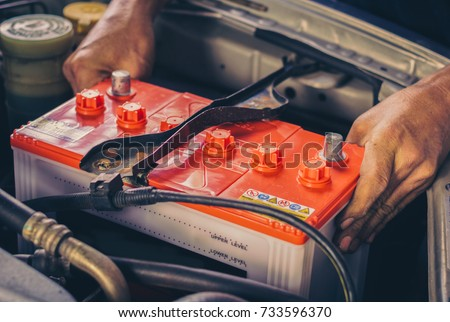 Photo of  A car mechanic replaces a battery