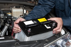 A car mechanic replaces a battery during maintenance.