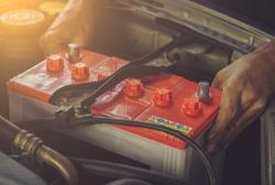 A car mechanic replaces a battery / soft focus picture