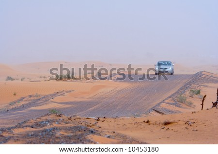 A car moving along a desert road. Visibility slightly limited by sand in midair.