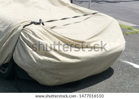 A car parked with a a protective cover #1477016510
