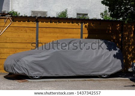 A car parked with protective cover silver. Car under a protective cover parked in the courtyard in sun weather, summer. car on the street under the fabric #1437342557